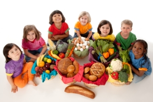 A high angle image of a diverse group of children holding baskets with the food groups of fruits, vegetables, dairy, meat, and grains.